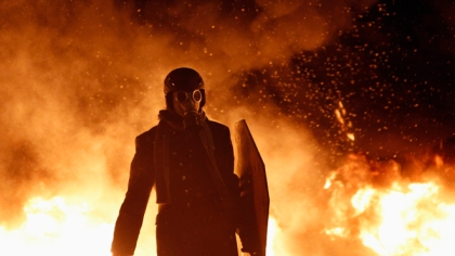 A pro-European protester wears a gas mask during street violence in Kiev